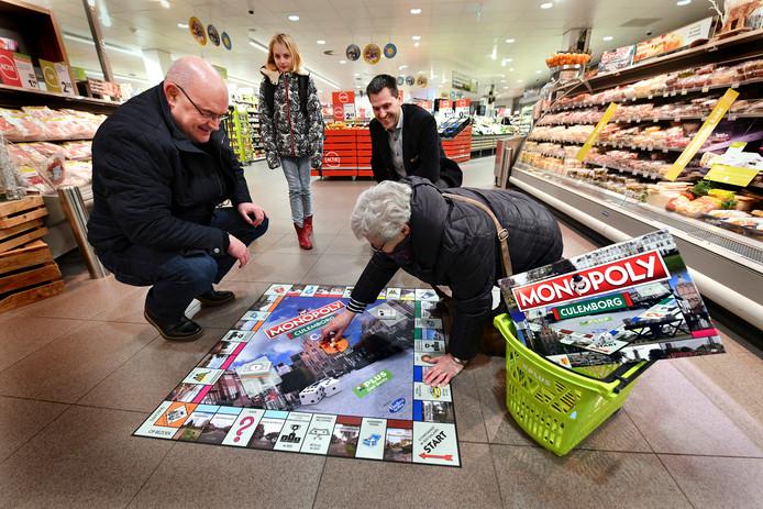 Culemborger Hans van Diejen speelt met zijn schoonmoeder Marlies Brocatus een potje Culemborgs Monopoly op een groot bord midden in supermarkt PLUS. Op de achtergrond eigenaar Giel Smits.