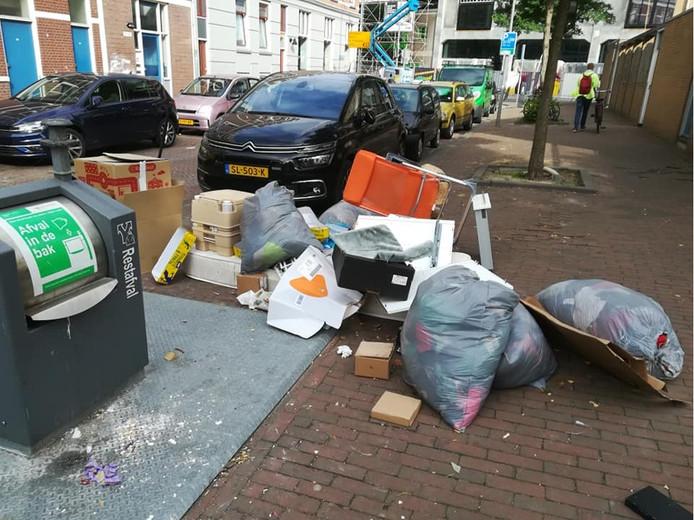 Wie deze foto van Dick van Bergem ziet, denkt dat er op Katendrecht meer vuil naast de container ligt dan erin.