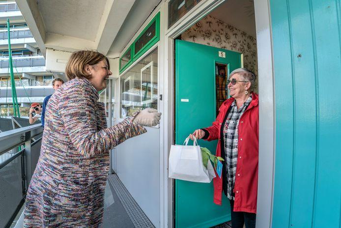 Burgemeester Marja van Bijsterveldt helpt bij de actie in een seniorencomplex aan de Diepenbrockstraat.