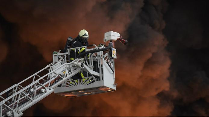 Een brandweerman gaat de vlammenzee te lijf.