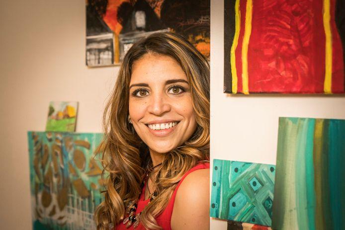 Aliana Almao temidden van door haar geschilderde doeken.