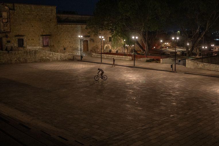 Een jongen speelt met zijn fiets op een verlaten plein. Beeld Alejandro Cegarra