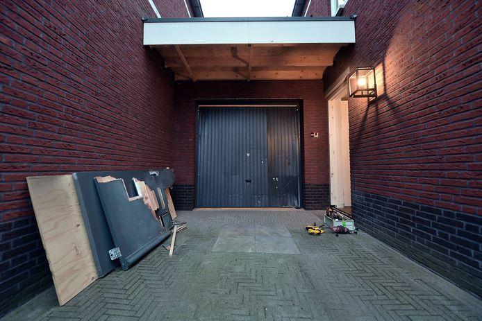 De met een vuurwerkbom verwoeste deur ligt in stukken op de oprit van de burgemeester van Woensdrecht. Het gat is vervangen door een houten plaat.