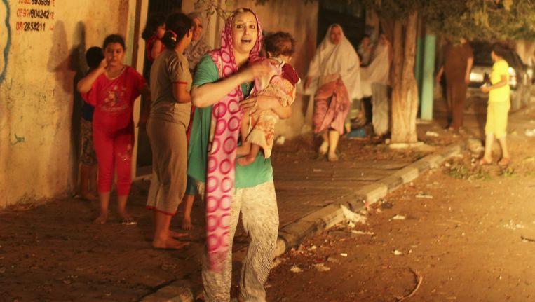 Palestijnen ontvluchten hun huizen na wat volgens ooggetuigen een Israëlische luchtaanval was. Een kind en een vrouw zouden de eerste burgerslachtoffers zijn sinds de verbreking van de wapenstilstand. Beeld reuters