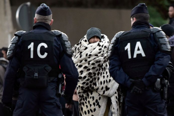 Franse agenten bij de ontruiming van het kamp La Chapelle bij Parijs. 1600 migranten werden geëvacueerd.