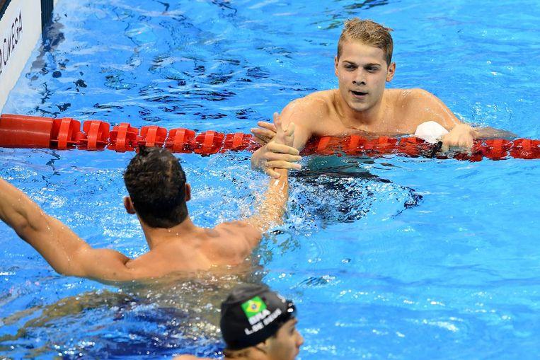 Michael Phelps met de Hongaar Tamas Kenderesi. Beeld getty