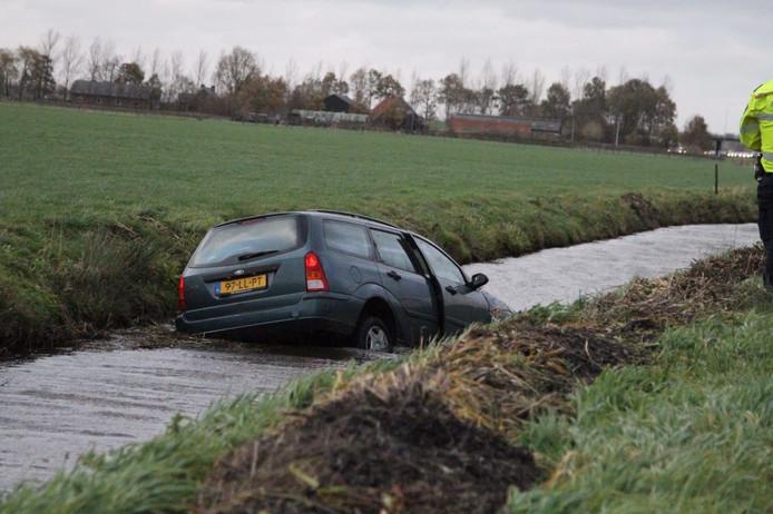 Een auto raakte op de A28 bij Nijkerk door de harde wind van de weg en belandde in de sloot. De inzittenden raakten niet gewond. Foto: News United.