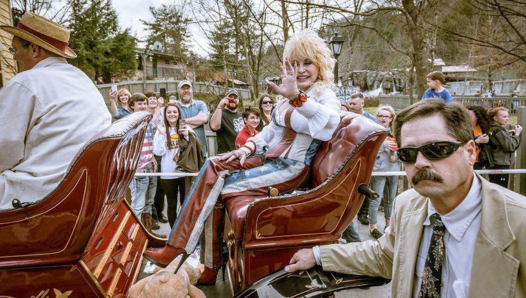 Countryster Dolly Parton, gehuld in kleding geënt op de Amerikaanse vlag, wordt rondgereden in een antieke auto in haar eigen Dollywood in Tennessee. Beeld Jurriaan Teulings