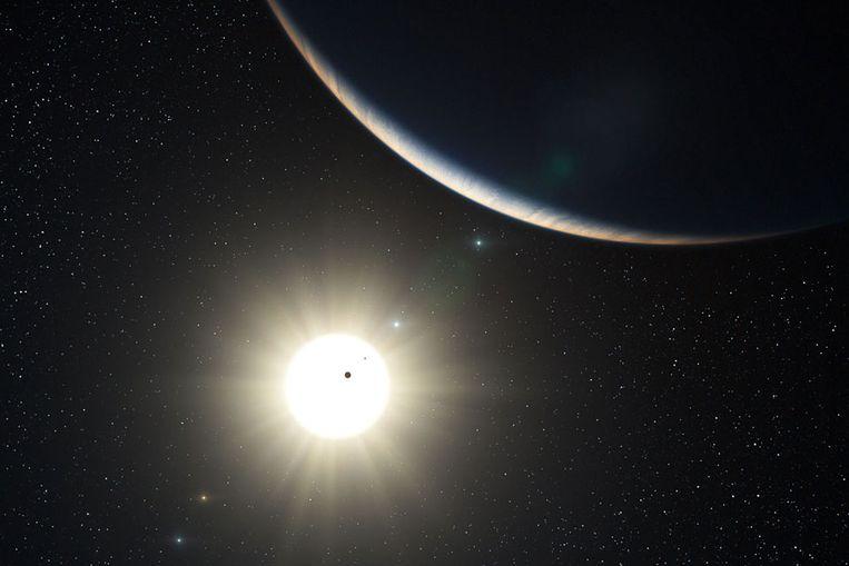 Een artistieke impressie van het planetenstelsel in het sterrenbeeld Waterman, met zicht op de ster waar de planeten omheen draaien. (Beeld ESA) Beeld
