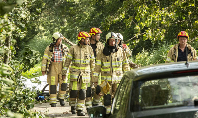 Hulpdiensten bij een ongeval waarbij een fietser onder een boom kwam. De fietser is overleden.