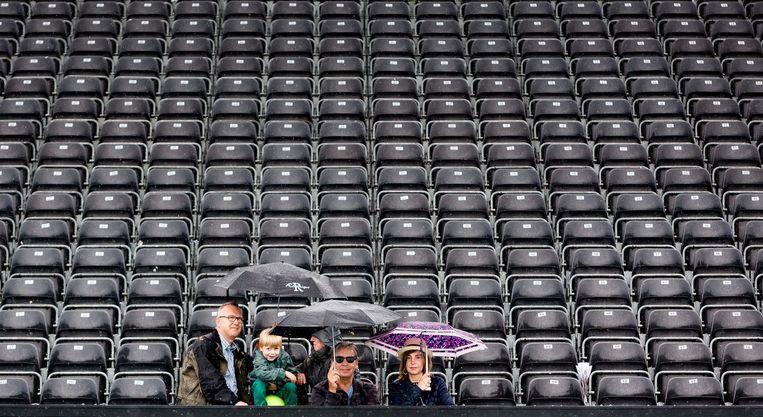 Toeschouwers wachten op de tribune tijdens de regenpauze in de finale bij de vrouwen. Beeld Freek Van Den Bergh