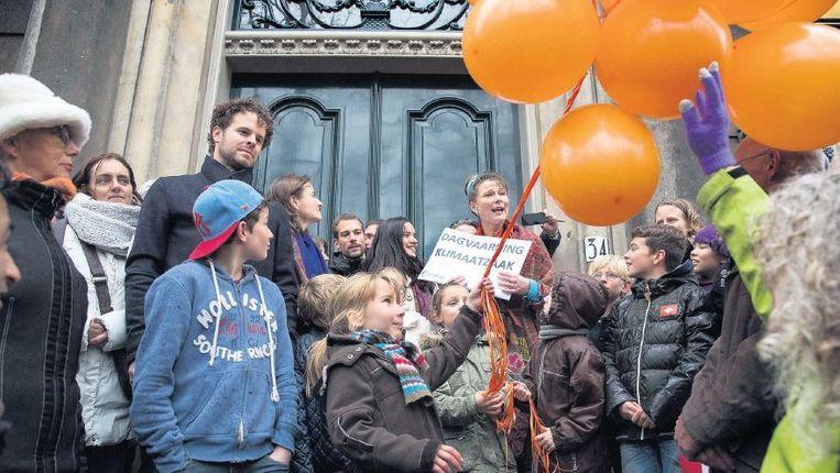 Urgenda-boegbeeld Marjan Minnesma (midden, met rode jas) met medestanders bij het gebouw van de Hoge Raad in Den Haag. Beeld Werry Crone