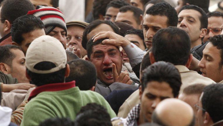 Betogers grijpen een man van wie zij denken dat hij pro-Mubarak is. Beeld ap