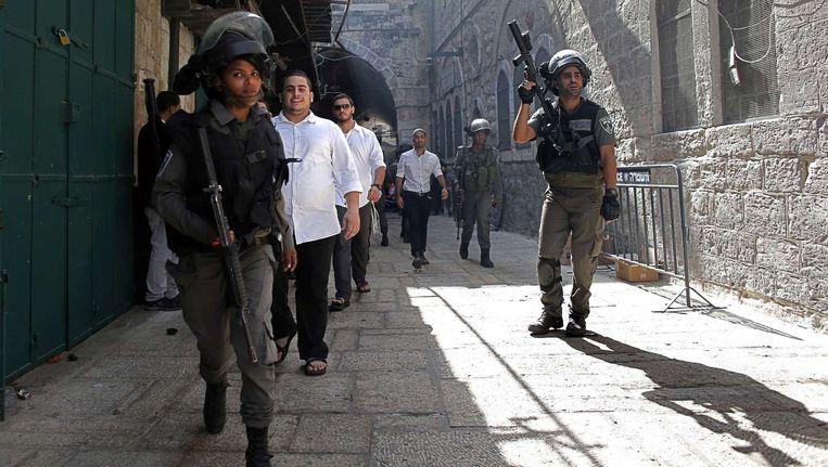 Israëlische veiligheidstroepen begeleiden joodse gelovigen bij de westmuur van de joodse tempel in Jeruzalem. Beeld afp