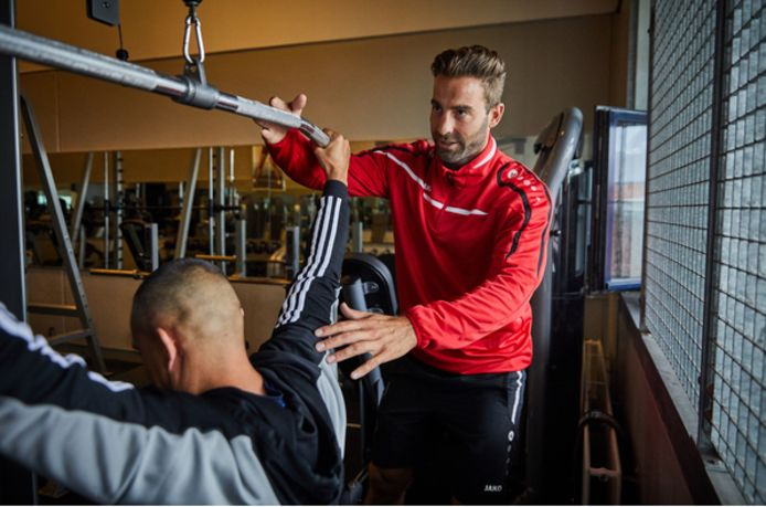 Sportinstructeur Daniel Wigman helpt een gedetineerde op de juiste manier een fitnessoefening te doen. De sportzaal heeft tralies.
