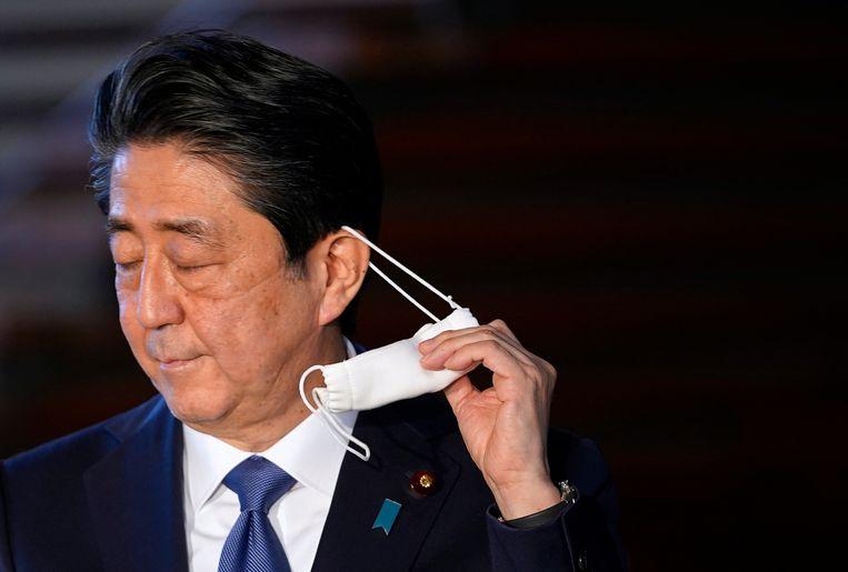 Premier Abe, vlak voor hij arriveert op de persconferentie waar hij een megasteunpakket aankondigt.  Beeld null
