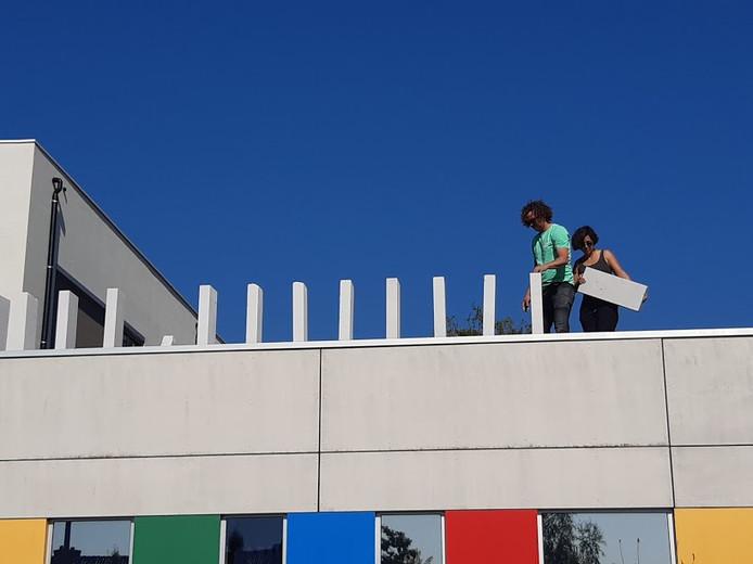 Zelf boven op het dak van de school komen domino's