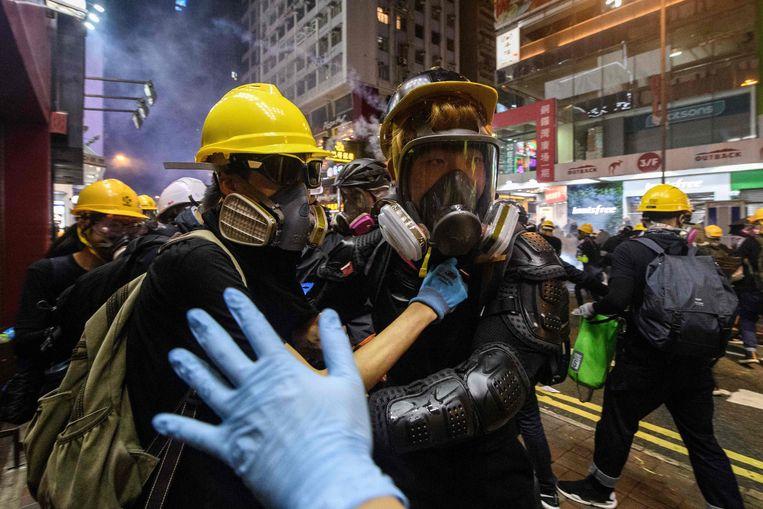 Een hulpverlener gebaart naar mensen die met traangas bespoten zijn in Hongkong.