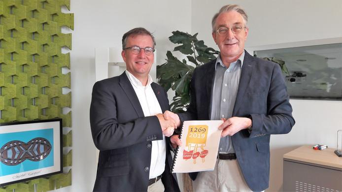 Voorzitter Bert Branderhorst (rechts) overhandigt het draaiboek voor 750 jaar Loon op Zand aan wethouder Kees Grootswagers.