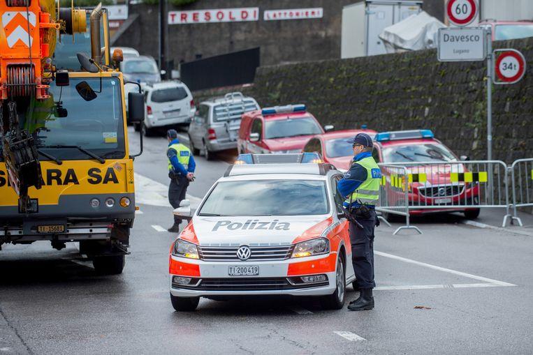 De politie zet een weg af bij het dorpje Davesco-Soragno, in de buurt van Lugano. In Lugano ontstond een modderstroom als gevolg van zware regenval. Beeld ap
