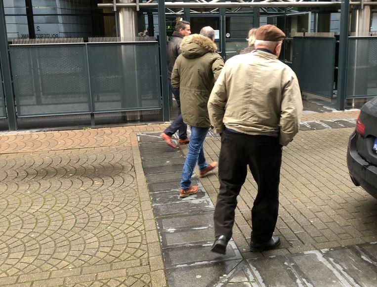 Beklaagde E.V.H. (rechts) bij het verlaten van de politierechtbank