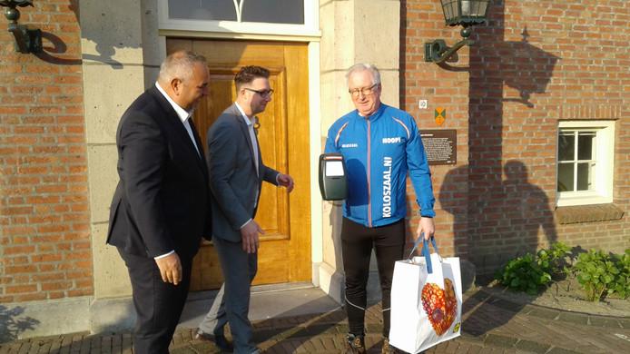 De wethouders John van Vugt en Mike Hofkens zwaaien Christ Mol uit bij zijn tocht langs tweeduizend huizen adressen in Raamsdonkveer om te collecteren voor Nationaal Kinderhulp Nederland.