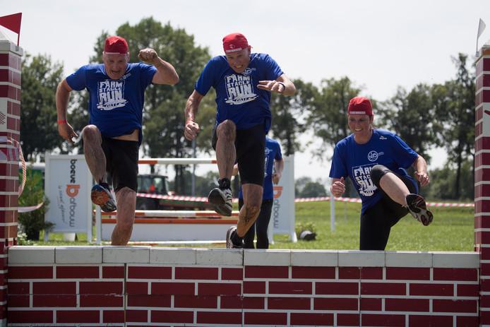 Deelnemers aan de Farmstacle Run nemen een hindernis op het concoursterrein.