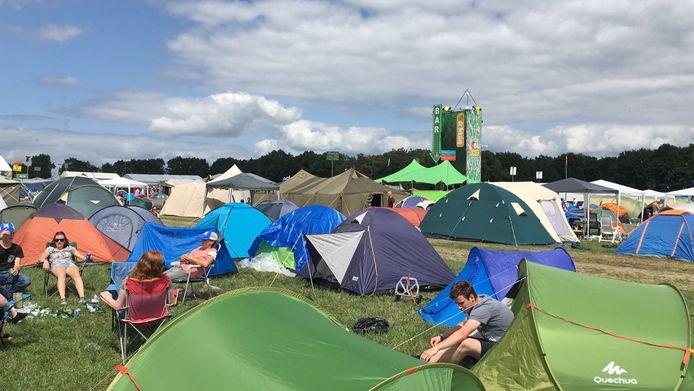 Bezoekers zijn bezig met het opzetten van hun tent op het kampeerterrein van de Zwarte Cross.