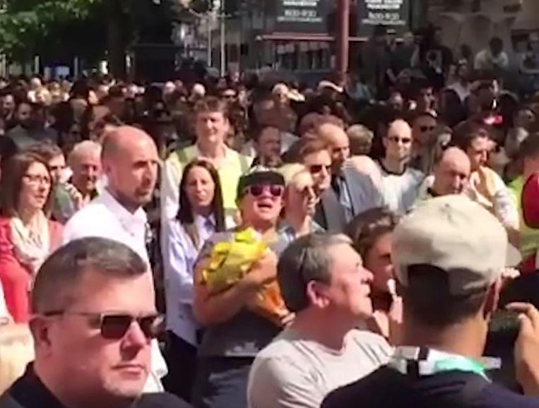 Lydia Bernsmeier-Rullow (met pet en zonnebril) tussen de mensen op St. Ann's Square Beeld Screenshot