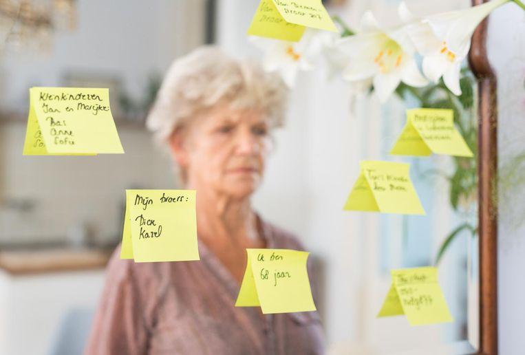 Een demente vrouw bekijkt notities op een spiegel.  Beeld ANP