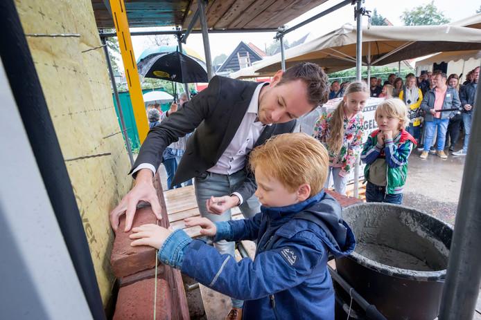 GEERTRUIDENBERG Jonge aankomende bewoners van de in aanbouw zijnde woningen aan de Venestraat in Geertruidenberg, helpen wethouder Kevin van Oort met het metselen van de 'eerste' steen.