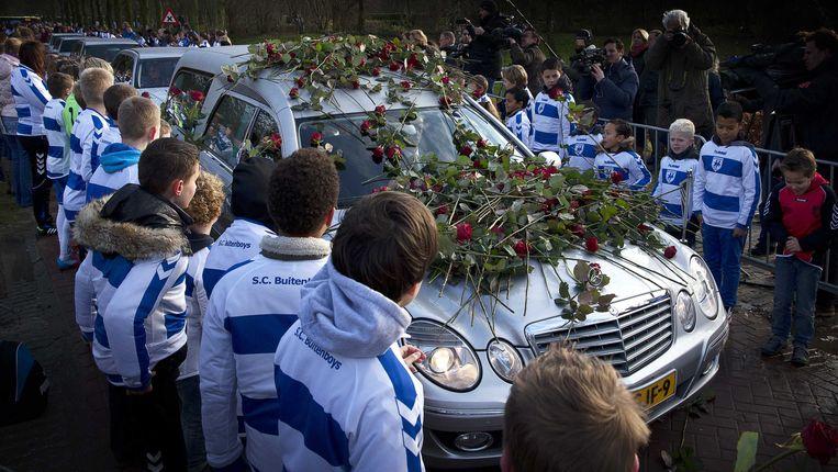 De auto met daarin het lichaam van de omgekomen grensrechter Richard Nieuwenhuizen rijdt bij het crematorium door een erehaag van jeugdspelers van SC Buitenboys. Beeld ANP
