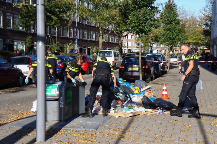 De politie onderzoekt een afvalbak na de steekpartij.