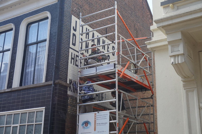 Het restaureren van de gevelreclame aan de Nieuwlandstraat.