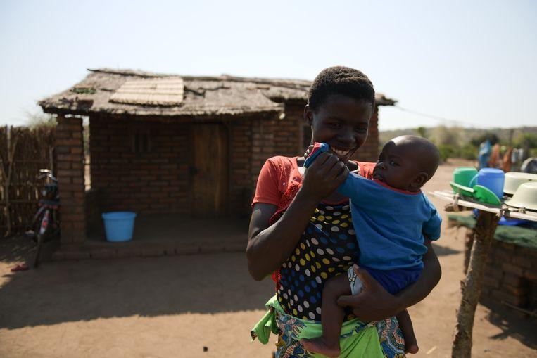 Violet Wilson (26) en haar zoontje (5 maanden) bij hun nieuwe stenen huis, dat beter beschermt tegen de muggen die malaria overbrengen Beeld Thoko Chikondi