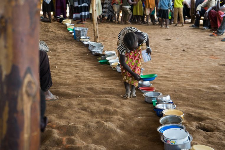 Een Congolese vluchteling sluit in een kamp in Oeganda met haar bord aan voor het eten. Beeld Getty Images