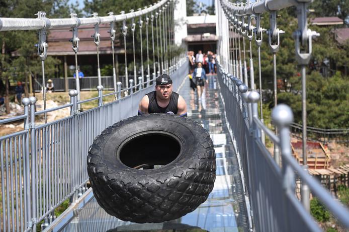 Op de glazen brug in Pingjiang doet een Chinees mee aan een 'bandenflip'-wedstrijd. Foto Stringer
