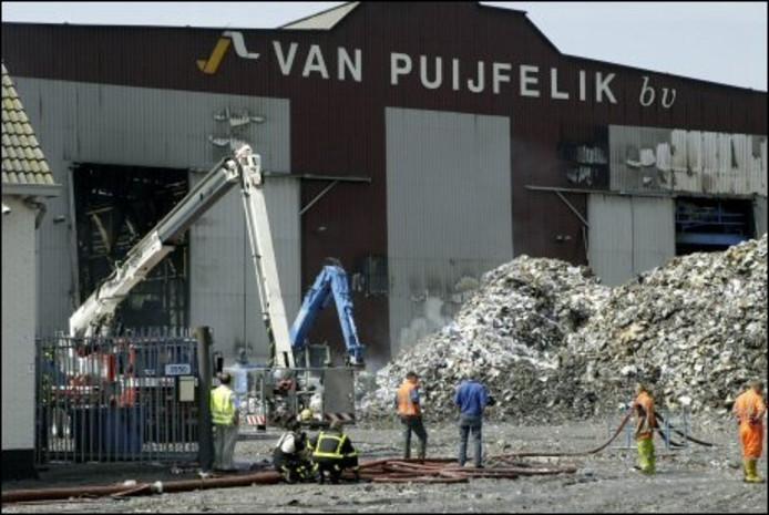 De brandweer heeft nog volop werk, de dag na de grote brand bij Van Puijfelik. FOTO PETER ROEK