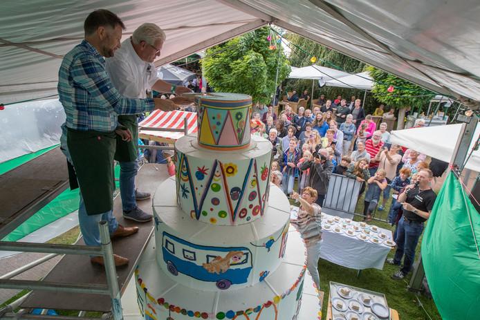 In 2017 sneed wijlen Hans Egelie (wit overhemd) samen met burgemeester Martijn Dadema een metershoge grote taart aan. Waarnemend voorzitter Gerben Korten noemt Egelie de Haarlemmerolie van de Pompdagen.