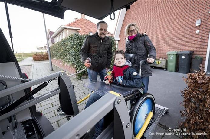 Boaz en zijn ouders Christiaan en Marjolein zijn dolblij met de nieuwe bus.