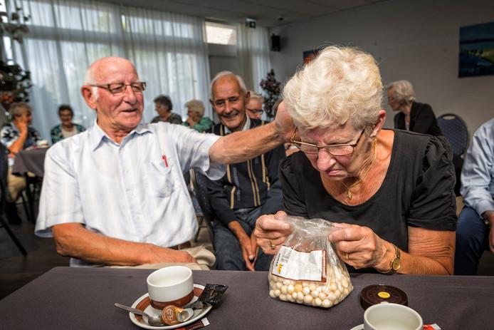 Annie Paardekooper (81) ruikt aan een zakje overjarige borrelnootjes