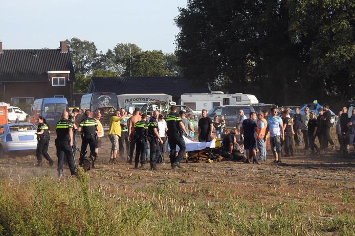 Politie en hulpdiensten bekommeren zich om gewonden nadat een deelnemer van de autocross in Leende inreed op het publiek. De grijze wagen staat uiterst links.