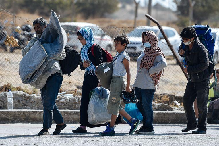 Een familie neemt hun schamele bezittingen mee naar een nieuw tijdelijk kamp. Beeld Hollandse Hoogte / AFP