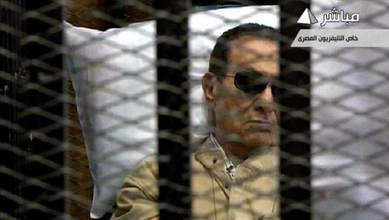 Videobeeld van de Egyptische oud-president Hosni Mubarak die wacht op zijn vonnis in de rechtbank. Beeld ANP