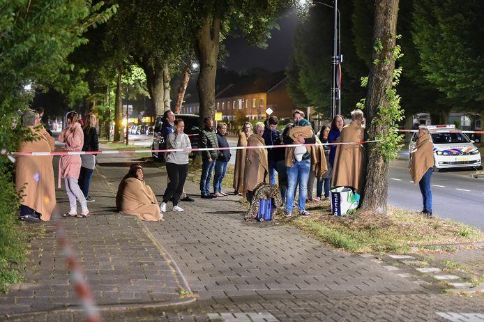 Met dekentjes om staan bewoners van een flatgebouw aan de Anklaarseweg in Apeldoorn 's nachts in de kou, nadat brand is uitgebroken in een van de woningen.