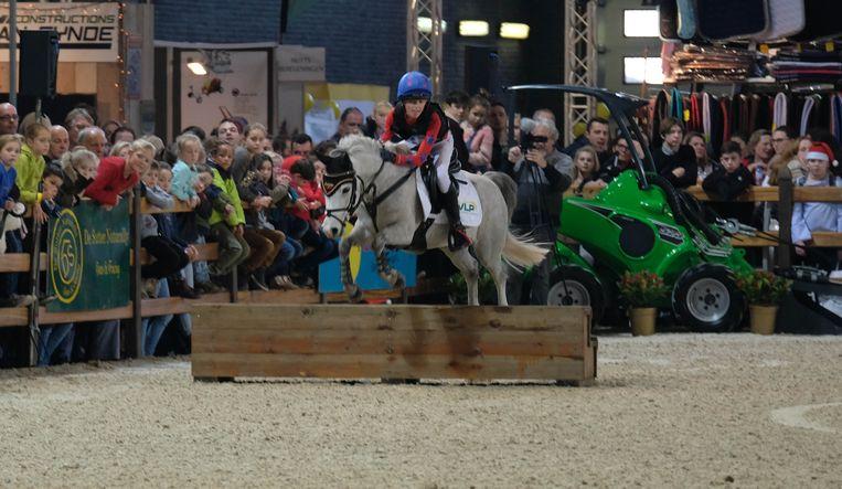 Jonge bezoekers kijken toe vanaf de zijlijn terwijl een deelnemer met een klein paard over de hindernissen springt.
