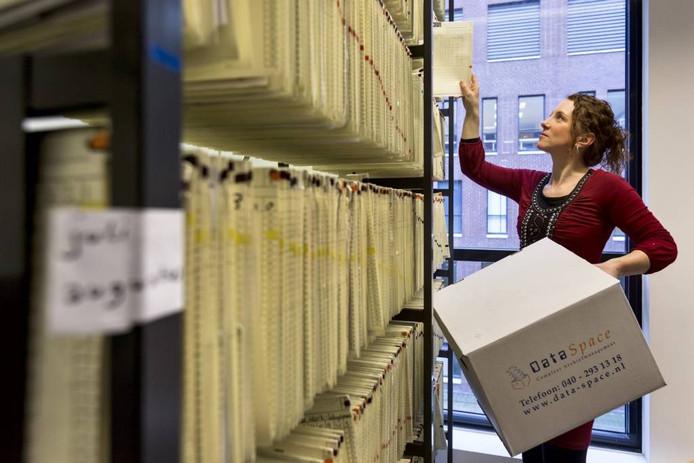 Een medewerkster van Data Space laadt in het JBZ dossiermappen in een verhuisdoos.