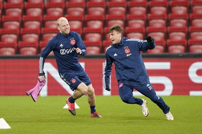 Davy Klaassen (l) en Nicolás Tagliafico van Ajax hebben plezier tijdens de training op Anfield, een dag voor de belangrijke wedstrijd tegen Liverpool.
