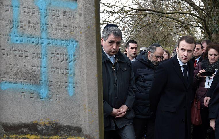 De Franse president Macron bezoekt een Joodse begraafplaats waar de graven zijn beklad met swastika's. Beeld REUTERS