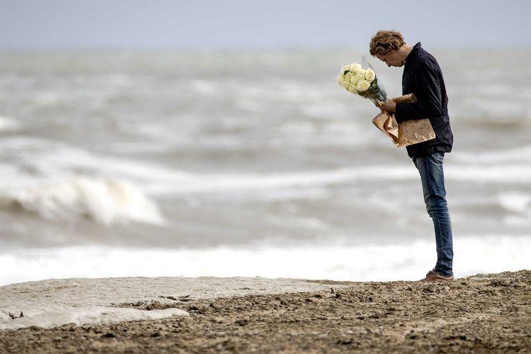 Een man houdt bloemen vast bij de kust van Scheveningen. Hij herdenkt de slachtoffers van het surfdrama.